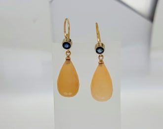 Gouden oorhangers met maansteen en saffier.