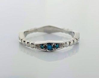 Witgouden aanschuifring met blauwe diamant.